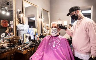 COLOGNE, GERMANY - MAY 04: Felix Hohleich serves a client at Gentlemen Barber Clubs that opened today for the first time since March during the novel coronavirus crisis on May 4, 2020 in Cologne, Germany. Barber shops and hair salons are reopening this week nationwide as authorities carefully lift lockdown measures that had been imposed to stem the spread of the virus. (Photo by Lars Baron/Getty Images)