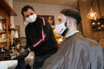 BERLIN, GERMANY - MAY 04: A barber tends to a customer as both of them wear protective face masks at a barber shop open for the first day since March during the novel coronavirus crisis on May 4, 2020 in Berlin, Germany. Barber shops and hair salons are reopening this week nationwide as authorities carefully lift lockdown measures that had been imposed to stem the spread of the virus. (Photo by Sean Gallup/Getty Images)