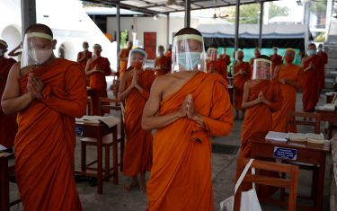 epa08401679 Novice Thai Buddhist monks wearing face shields and protective face masks, attend a lesson at Wat Molilokayaram monastic educational institute in Bangkok, Thailand, 16 April 2020 (issued 05 May 2020). The traditional Buddhist temples in Thailand have adopted innovative measures like setting up sanitizing tunnels and making masks to join the fight against COVID-19. Not only have the monks added an orange mask to their attire - which has remained largely unchanged since the time of Buddha (2,500 years ago) - but also make their own sanitizers. They have also been distributing food to those who have lost their incomes due to the crisis. Several monasteries have completely stopped going out for morning alms while some have reduced the numbers of monks going outside, while wearing protective masks and sometimes face shields in an effort to help prevent the spread of the COVID 19 disease pandemic caused by the SARS CoV-2 coronavirus.  EPA/DIEGO AZUBEL  ATTENTION: This Image is part of a PHOTO SET