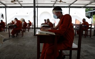 epa08401678 Seated on desks arranged to maintain social distancing, novice Thai Buddhist monks wearing face shields and protective face masks, attend a lesson at Wat Molilokayaram monastic educational institute in Bangkok, Thailand, 16 April 2020 (issued 05 May 2020). The traditional Buddhist temples in Thailand have adopted innovative measures like setting up sanitizing tunnels and making masks to join the fight against COVID-19. Not only have the monks added an orange mask to their attire - which has remained largely unchanged since the time of Buddha (2,500 years ago) - but also make their own sanitizers. They have also been distributing food to those who have lost their incomes due to the crisis. Several monasteries have completely stopped going out for morning alms while some have reduced the numbers of monks going outside, while wearing protective masks and sometimes face shields in an effort to help prevent the spread of the COVID 19 disease pandemic caused by the SARS CoV-2 coronavirus.  EPA/DIEGO AZUBEL  ATTENTION: This Image is part of a PHOTO SET