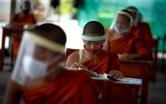 epa08401680 Seated on desks arranged to maintain social distancing, novice Thai Buddhist monks wearing face shields and protective face masks, attend a lesson at Wat Molilokayaram monastic educational institute in Bangkok, Thailand, 16 April 2020 (issued 05 May 2020). The traditional Buddhist temples in Thailand have adopted innovative measures like setting up sanitizing tunnels and making masks to join the fight against COVID-19. Not only have the monks added an orange mask to their attire - which has remained largely unchanged since the time of Buddha (2,500 years ago) - but also make their own sanitizers. They have also been distributing food to those who have lost their incomes due to the crisis. Several monasteries have completely stopped going out for morning alms while some have reduced the numbers of monks going outside, while wearing protective masks and sometimes face shields in an effort to help prevent the spread of the COVID 19 disease pandemic caused by the SARS CoV-2 coronavirus.  EPA/DIEGO AZUBEL  ATTENTION: This Image is part of a PHOTO SET