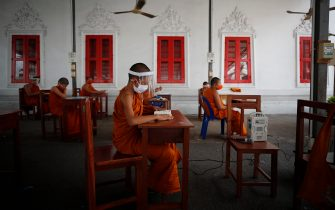 epa08401681 Seated on desks arranged to maintain social distancing, novice Thai Buddhist monks wearing face shields and protective face masks, attend a lesson at Wat Molilokayaram monastic educational institute in Bangkok, Thailand, 16 April 2020 (issued 05 May 2020). The traditional Buddhist temples in Thailand have adopted innovative measures like setting up sanitizing tunnels and making masks to join the fight against COVID-19. Not only have the monks added an orange mask to their attire - which has remained largely unchanged since the time of Buddha (2,500 years ago) - but also make their own sanitizers. They have also been distributing food to those who have lost their incomes due to the crisis. Several monasteries have completely stopped going out for morning alms while some have reduced the numbers of monks going outside, while wearing protective masks and sometimes face shields in an effort to help prevent the spread of the COVID 19 disease pandemic caused by the SARS CoV-2 coronavirus.  EPA/DIEGO AZUBEL  ATTENTION: This Image is part of a PHOTO SET