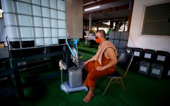 epa08401693 A Thai Buddhist monk wearing a protective mask fills containers with sodium hypochlorite for disinfecting at Wat Chak Daeng in Samut Prakan, Thailand, 22 April 2020 (issued 05 May 2020). The traditional Buddhist temples in Thailand have adopted innovative measures like setting up sanitizing tunnels and making masks to join the fight against COVID-19. Not only have the monks added an orange mask to their attire - which has remained largely unchanged since the time of Buddha (2,500 years ago) - but also make their own sanitizers. They have also been distributing food to those who have lost their incomes due to the crisis.  EPA/DIEGO AZUBEL  ATTENTION: This Image is part of a PHOTO SET