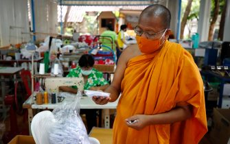 epa08401683 Thai Buddhist monk Phra Maha Pranom Dhammalangkaro checks a face mask at the face mask workshop inside Wat Chak Daeng in Samut Prakan, Thailand, 22 April 2020 (issued 05 May 2020). The traditional Buddhist temples in Thailand have adopted innovative measures like setting up sanitizing tunnels and making masks to join the fight against COVID-19. Not only have the monks added an orange mask to their attire - which has remained largely unchanged since the time of Buddha (2,500 years ago) - but also make their own sanitizers. They have also been distributing food to those who have lost their incomes due to the crisis.  EPA/DIEGO AZUBEL  ATTENTION: This Image is part of a PHOTO SET