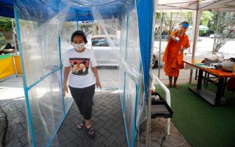 epa08401689 A visitor walks through a makeshift disinfecting chamber upon entering Wat Chak Daeng in Samut Prakan, Thailand, 22 April 2020 (issued 05 May 2020). The traditional Buddhist temples in Thailand have adopted innovative measures like setting up sanitizing tunnels and making masks to join the fight against COVID-19. Not only have the monks added an orange mask to their attire - which has remained largely unchanged since the time of Buddha (2,500 years ago) - but also make their own sanitizers. They have also been distributing food to those who have lost their incomes due to the crisis.  EPA/DIEGO AZUBEL  ATTENTION: This Image is part of a PHOTO SET
