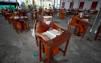 epa08401688 Seated on desks arranged to maintain social distancing, novice Thai Buddhist monks wearing face shields and protective face masks, attend a lesson at Wat Molilokayaram monastic educational institute in Bangkok, Thailand, 16 April 2020 (issued 05 May 2020). The traditional Buddhist temples in Thailand have adopted innovative measures like setting up sanitizing tunnels and making masks to join the fight against COVID-19. Not only have the monks added an orange mask to their attire - which has remained largely unchanged since the time of Buddha (2,500 years ago) - but also make their own sanitizers. They have also been distributing food to those who have lost their incomes due to the crisis. Several monasteries have completely stopped going out for morning alms while some have reduced the numbers of monks going outside, while wearing protective masks and sometimes face shields in an effort to help prevent the spread of the COVID 19 disease pandemic caused by the SARS CoV-2 coronavirus.  EPA/DIEGO AZUBEL  ATTENTION: This Image is part of a PHOTO SET
