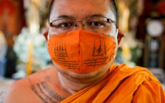 epa08401690 Thai Buddhist monk Phra Chamnanwet poses with a mask he designed with sacred mantras as an added layer of protection at Wat Chak Daeng in Samut Prakan, Thailand, 22 April 2020 (issued 05 May 2020). The traditional Buddhist temples in Thailand have adopted innovative measures like setting up sanitizing tunnels and making masks to join the fight against COVID-19. Not only have the monks added an orange mask to their attire - which has remained largely unchanged since the time of Buddha (2,500 years ago) - but also make their own sanitizers. They have also been distributing food to those who have lost their incomes due to the crisis.  EPA/DIEGO AZUBEL  ATTENTION: This Image is part of a PHOTO SET