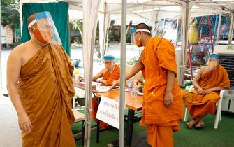 epa08401695 Thai Buddhist monks wear protective masks and face shields at the entrance check point to Wat Chak Daeng in Samut Prakan, Thailand, 22 April 2020 (issued 05 May 2020). The traditional Buddhist temples in Thailand have adopted innovative measures like setting up sanitizing tunnels and making masks to join the fight against COVID-19. Not only have the monks added an orange mask to their attire - which has remained largely unchanged since the time of Buddha (2,500 years ago) - but also make their own sanitizers. They have also been distributing food to those who have lost their incomes due to the crisis.  EPA/DIEGO AZUBEL  ATTENTION: This Image is part of a PHOTO SET
