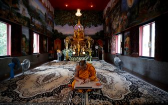 epa08401692 Thai Buddhist monk Phra Chamnanwet writes sacred mantras on protective masks as an added layer of protection at Wat Chak Daeng in Samut Prakan, Thailand, 22 April 2020 (issued 05 May 2020). The traditional Buddhist temples in Thailand have adopted innovative measures like setting up sanitizing tunnels and making masks to join the fight against COVID-19. Not only have the monks added an orange mask to their attire - which has remained largely unchanged since the time of Buddha (2,500 years ago) - but also make their own sanitizers. They have also been distributing food to those who have lost their incomes due to the crisis.  EPA/DIEGO AZUBEL  ATTENTION: This Image is part of a PHOTO SET