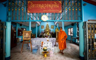 epaselect epa08401684 Thai Buddhist monk Phra Maha Pranom Dhammalangkaro stands next to water bottles blessed by the temple monks inside Wat Chak Daeng in Samut Prakan, Thailand, 22 April 2020.(issued 05 May 2020). The traditional Buddhist temples in Thailand have adopted innovative measures like setting up sanitizing tunnels and making masks to join the fight against COVID-19. Not only have the monks added an orange mask to their attire - which has remained largely unchanged since the time of Buddha (2,500 years ago) - but also make their own sanitizers. They have also been distributing food to those who have lost their incomes due to the crisis.  EPA/DIEGO AZUBEL  ATTENTION: This Image is part of a PHOTO SET