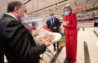 Queen Mathilde of Belgium (R) wearing a protective mask receives a present as she visits the Carrefour supermarkets of Mestdagh groupe in Gerpinnes, on May 6, 2020 during a novel coronavirus (COVID-19) pandemic. (Photo by Benoit DOPPAGNE / BELGA / AFP) / Belgium OUT (Photo by BENOIT DOPPAGNE/BELGA/AFP via Getty Images)
