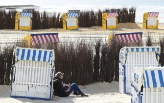 CUXHAVEN, GERMANY - MAY 06: A person sits by a beach chairs stand ready for vacationers at Duhne beach during the coronavirus crisis on May 6, 2020 near Cuxhaven, Germany. German states that contain popular holiday destinations and that are economically dependant on tourism, including Lower Saxony, Mecklenburg-Western Pomerania, Schleswig-Holstein and Bavaria, have announced an easing of lockdown measures in order to let hotels, restaurants and beaches reopen for visitors in coming weeks. (Photo by Stuart Franklin/Getty Images)