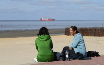 CUXHAVEN, GERMANY - MAY 06: People sit on the each at Duhne beach during the coronavirus crisis on May 6, 2020 near Cuxhaven, Germany. German states that contain popular holiday destinations and that are economically dependant on tourism, including Lower Saxony, Mecklenburg-Western Pomerania, Schleswig-Holstein and Bavaria, have announced an easing of lockdown measures in order to let hotels, restaurants and beaches reopen for visitors in coming weeks. (Photo by Stuart Franklin/Getty Images)