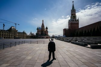 A law enforcement officer stands guard on the deserted Red Square in front of St. Basil's Cathedral and the Kremlin's Spasskaya Tower in downtown Moscow on April 22, 2020, during a strict lockdown in Russia to stop the spread of the novel coronavirus COVID-19. (Photo by Dimitar DILKOFF / AFP) (Photo by DIMITAR DILKOFF/AFP via Getty Images)