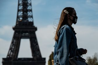 A woman wearing a face mask walks near the Eiffel Tower in Paris on April 7, 2020, during the 22nd day of a lockdown in France aimed at curbing the spread of the COVID-19 pandemic, caused by the novel coronavirus. (Photo by BERTRAND GUAY / AFP) (Photo by BERTRAND GUAY/AFP via Getty Images)