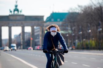 A cyclist wearing a protective mask pedals along an almost deserted 17th June street leading up to Brandenburger gate in Berlin on April 1, 2020 as Germany continues its battle against the Covid-19 corona virus. - The avenue leading up to the landmark Brandenburger Gate is normally one of the busiest stretches of road in the German capital but are now largely empty as people work from home. (Photo by Odd ANDERSEN / AFP) (Photo by ODD ANDERSEN/AFP via Getty Images)
