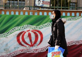 An Iranian woman wearing a mask walks past a mural displaying her national flag in Tehran on March 4, 2020. - Iran has scrambled to halt the rapid spread of the COVID-19 virus, shutting schools and universities, suspending major cultural and sporting events, and cutting back on work hours. (Photo by ATTA KENARE / AFP) (Photo by ATTA KENARE/AFP via Getty Images)