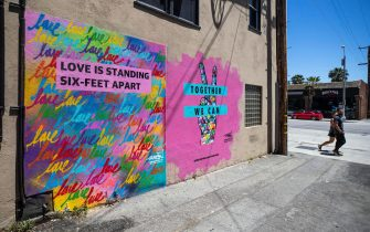 epa08406397 A couple walks past a mural by Mr. Rojas reading 'Love is Standing Six-Feet Apart' and 'Together We can' amid the coronavirus pandemic in Santa Monica, California, USA, 06 May 2020.  EPA/ETIENNE LAURENT