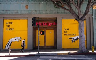 epa08406399 A couple wearing face masks walks the boarded clothing shop 'Wasteland' displaying a mural by Corie Mattie that reads 'After the Plague Came the Renaissance' amid the coronavirus pandemic in Santa Monica, California, USA, 06 May 2020.  EPA/ETIENNE LAURENT
