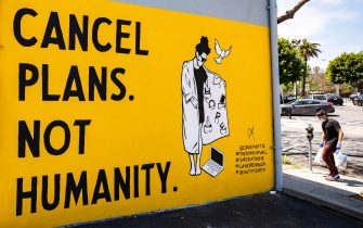 epa08406401 A man carrying groceries and wearing a face mask walks past a mural by Corie Mattie that reads 'Cancel Plans Not Humanity' amid the coronavirus pandemic in Los Angeles, California, USA, 06 May 2020.  EPA/ETIENNE LAURENT