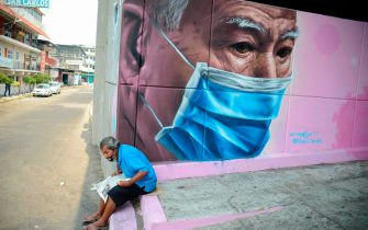 TOPSHOT - A man sits next to a mural of a man wearing a face mask in Acapulco, Guerrero state, Mexico, on May 6, 2020, amid the new coronavirus pandemic. - More than 15,000 people have been killed by the novel coronavirus in Latin America and the Caribbean as of 0230 GMT Wednesday, according to an AFP tally based on official reports. Topping the death toll list is Brazil, with 7,921 fatalities and 114,715 cases; followed by Mexico with 2,271 fatalities and Ecuador with 1,569 deaths. (Photo by FRANCISCO ROBLES / AFP)