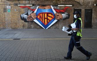 epa08405136 A masked man passes a mural by Lionel Stanhope in support of Britain's National Health Service (NHS) in London, Britain, 06 May 2020. Countries around the world are taking increased measures to stem the widespread of the SARS-CoV-2 coronavirus which causes the Covid-19 disease.  EPA/NEIL HALL