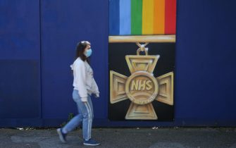 """A pedestrian passes a mural depicting a Victoria Cross, Britain's highest award for valour, with """"NHS"""" written in the middle with a rainbow ribbon to honour NHS staff who continue to work caring for patients during the coronavirus pandemic in London on May 6, 2020. - Britain's death toll from the coronavirus has topped 32,000, according to an updated official count released Tuesday, pushing the country past Italy to become the second-most impacted after the United States. The new toll, from the Office for National Statistics (ONS) and regional health bodies, has not yet been incorporated into the government's daily figures, which records the current number of deaths as 29,427. (Photo by ISABEL INFANTES / AFP) / RESTRICTED TO EDITORIAL USE - MANDATORY MENTION OF THE ARTIST UPON PUBLICATION - TO ILLUSTRATE THE EVENT AS SPECIFIED IN THE CAPTION"""