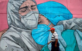 TOPSHOT - A man walks past a coronavirus-related mural, in Acapulco, Guerrero state, Mexico, on May 1, 2020. (Photo by FRANCISCO ROBLES / AFP)