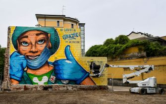 Street artist Lapo Fatai (R) finishes a mural in honor of medical workers, next to the Auxological San Luca hospital on April 30, 2020 in Milan during the country's lockdown aimed at curbing the spread of the COVID-19 infection, caused by the novel coronavirus. (Photo by Miguel MEDINA / AFP) / RESTRICTED TO EDITORIAL USE - MANDATORY MENTION OF THE ARTIST UPON PUBLICATION - TO ILLUSTRATE THE EVENT AS SPECIFIED IN THE CAPTION (Photo by MIGUEL MEDINA/AFP via Getty Images)