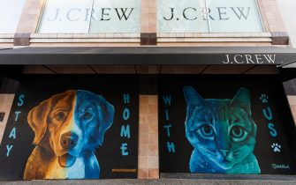 """VANCOUVER, BRITISH COLUMBIA - MAY 06: Murals of a dog and a cat reading """"Stay Home"""" and """"With Us"""" is on display on boarded up windows of J.Crew storefront on Robson Street during the coronavirus pandemic on May 06, 2020 in Vancouver, Canada. Robson Street, normally a popular tourist area in Vancouver is quiet as all non-essential retail has been closed to slow the spread of COVID-19. (Photo by Andrew Chin/Getty Images)"""