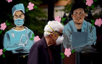 A man wearing a face mask walks past a mural in support of health workers in the window of a restaurant during the outbreak of COVID-19  in Arlington, Virginia on May 6, 2020. (Photo by Olivier DOULIERY / AFP) (Photo by OLIVIER DOULIERY/AFP via Getty Images)