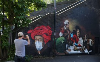 A man photographs murals by artist Lionel Stanhope depicting the 15th century painting 'Man in a Red Turban' by Flemish renaissance painter Jan van Eyck (L) and 'The Supper at Emmaus' by Italian painter Caravaggio (R) with the addition of blue nitrile gloves in south London on May 6, 2020 as life continues under a nationwide lockdown imposed to slow the spread of the novel coronavirus. - Britain's death toll from the coronavirus has topped 32,000, according to an updated official count released Tuesday, pushing the country past Italy to become the second-most impacted after the United States. The new toll, from the Office for National Statistics (ONS) and regional health bodies, has not yet been incorporated into the government's daily figures, which records the current number of deaths as 29,427. (Photo by ISABEL INFANTES / AFP) / RESTRICTED TO EDITORIAL USE - MANDATORY MENTION OF THE ARTIST UPON PUBLICATION - TO ILLUSTRATE THE EVENT AS SPECIFIED IN THE CAPTION (Photo by ISABEL INFANTES/AFP via Getty Images)