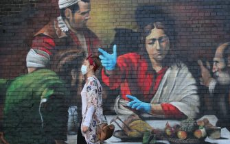 A woman stands in front of a mural by artist Lionel Stanhope depicting the painting ''The Supper at Emmaus' by Italian painter Caravaggio with the addition of blue nitrile gloves in south London on May 6, 2020 as life continues under a nationwide lockdown imposed to slow the spread of the novel coronavirus. - Britain's death toll from the coronavirus has topped 32,000, according to an updated official count released Tuesday, pushing the country past Italy to become the second-most impacted after the United States. The new toll, from the Office for National Statistics (ONS) and regional health bodies, has not yet been incorporated into the government's daily figures, which records the current number of deaths as 29,427. (Photo by ISABEL INFANTES / AFP) / RESTRICTED TO EDITORIAL USE - MANDATORY MENTION OF THE ARTIST UPON PUBLICATION - TO ILLUSTRATE THE EVENT AS SPECIFIED IN THE CAPTION (Photo by ISABEL INFANTES/AFP via Getty Images)