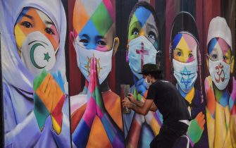 """Brazilian mural artist Eduardo Kobra works on his recent work """"Coexistence"""" -which shows children wearing face masks due to the new coronavirus, COVID-19, bearing symbols of different religions (L to R) Islam, Buddhism, Christianity, Judaism and Hinduism- in Itu, some 100 km from Sao Paulo, Brazil on April 25, 2020. (Photo by NELSON ALMEIDA / AFP) (Photo by NELSON ALMEIDA/AFP via Getty Images)"""