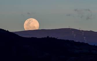 epa08406471 View of the full moon at dusk in Quito, Ecuador, 06 May 2020.  EPA/Jose Jacome