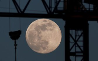 epa08406536 A full moon sits in the sky above buildings being constructed in Pamplona, Spain, 06 May 2020 (issued on 07 May 2020).  EPA/Jesus Diges