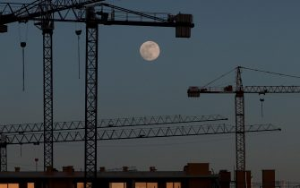 epa08406535 A full moon sits in the sky above buildings being constructed in Pamplona, Spain, 06 May 2020 (issued on 07 May 2020).  EPA/Jesus Diges
