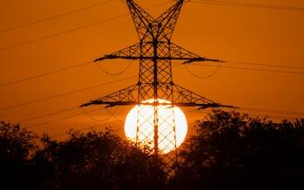 07 May 2020, Lower Saxony, Oldenburg: In the early morning, the sun rises behind an overhead line pylon. Photo: Mohssen Assanimoghaddam/dpa (Mohssen Assanimoghaddam / IPA/Fotogramma, Oldenburg - 2020-05-07) p.s. la foto e' utilizzabile nel rispetto del contesto in cui e' stata scattata, e senza intento diffamatorio del decoro delle persone rappresentate