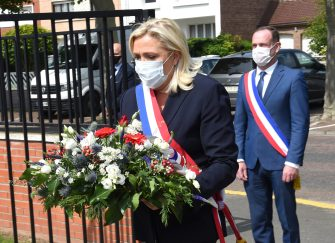 French far-right party Rassemblement National's (RN) President and member of Parliament Marine Le Pen (C) and RN mayor of Henin-Beaumont Steeve Briois (R) wearing a face mask lay a wreath to mark the 75th anniversary of the end of World War II on May 8, 2020, at the war memorial of Henin-Beaumont, eastern France. (Photo by FRANCOIS LO PRESTI / AFP) (Photo by FRANCOIS LO PRESTI/AFP via Getty Images)