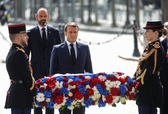 French President Emmanuel Macron (front) and French Prime Minister Edouard Philippe attend a ceremony to mark the end of World War II at the Arc de Triomphe in Paris on May 8, 2020. - A continent devastated by the coronavirus will mark the 75th anniversary of the end of World War II in Europe on May 8, 2020, as the economic destruction of the current global crisis was laid bare. Large-scale parades that had been envisaged to commemorate victory over the Nazis have been downsized as the world grapples with a fearsome new enemy that has killed 277,000 people and sickened more than 3.7 million. (Photo by CHARLES PLATIAU / POOL / AFP) (Photo by CHARLES PLATIAU/POOL/AFP via Getty Images)