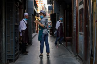 BEIJING, CHINA - MAY 08:  Chinese cooks wear a protective mask as they wait for customers outside a restaurant on May 8, 2020 in Beijing, China. Life in Beijing is slowly returning to normal following a city-wide lockdown on January 25 to contain the coronavirus (COVID-19) outbreak.  (Photo by Lintao Zhang/Getty Images)