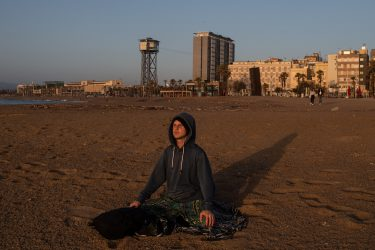 BARCELONA, SPAIN - MAY 08: A man practices yoga at dawn at La Barceloneta Beach opened for the first day since March 15 during the novel coronavirus crisis on May 08, 2020 in Barcelona, Spain. Permitted activities now include outdoor water sports such as surf, paddle surf or swimming from 6 - 10 AM and from 8 - 11 PM. Spain has had more than 220,000 confirmed cases of COVID-19 and over 26,000 reported deaths, although the rate has declined after weeks of lockdown measures. (Photo by David Ramos/Getty Images)