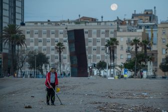 BARCELONA, SPAIN - MAY 08: A man uses a metal detector at dawn at La Barceloneta Beach opened for the first day since March 15 during the novel coronavirus crisis on May 08, 2020 in Barcelona, Spain. Permitted activities now include outdoor water sports such as surfing, paddle boarding or swimming from 6 - 10 AM and from 8 - 11 PM, with beaches only open for sporting activities such as running, working out or water sports. Spain has had more than 220,000 confirmed cases of COVID-19 and over 26,000 reported deaths, although the rate has declined after weeks of lockdown measures.  (Photo by David Ramos/Getty Images)