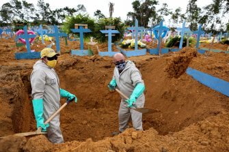 Brazilian Ulisses Xavier, 52, who has worked for 16 years at Nossa Senhora cemetery in Manaus, Brazil, digs a grave alongside a co-worker during their shift on May 8, 2020, amid the new coronavirus pandemic. - Xavier works 12 hours a day and supplements his income by making wooden crosses for graves. The cemetery has seen a surge in the number of new graves after the outbreak of COVID-19. (Photo by MICHAEL DANTAS / AFP) (Photo by MICHAEL DANTAS/AFP via Getty Images)