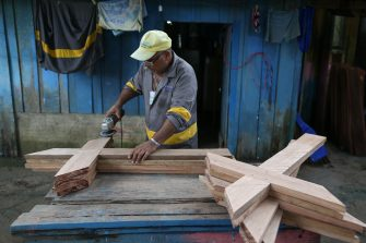 Brazilian Ulisses Xavier, 52, who has worked for 16 years at Nossa Senhora cemetery in Manaus, Brazil, makes wooden crosses at his house on May 7, 2020, amid the new coronavirus pandemic. - Xavier works 12 hours a day and supplements his income by making wooden crosses for graves. The cemetery has seen a surge in the number of new graves after the outbreak of COVID-19. (Photo by MICHAEL DANTAS / AFP) (Photo by MICHAEL DANTAS/AFP via Getty Images)