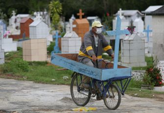 Brazilian Ulisses Xavier, 52, who has worked for 16 years at Nossa Senhora cemetery in Manaus, Brazil, rides a bike carrying a cross during his shift on May 7, 2020, amid the new coronavirus pandemic. - Xavier works 12 hours a day and supplements his income by making wooden crosses for graves. The cemetery has seen a surge in the number of new graves after the outbreak of COVID-19. (Photo by MICHAEL DANTAS / AFP) (Photo by MICHAEL DANTAS/AFP via Getty Images)
