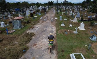 Brazilian Ulisses Xavier, 52, who has worked for 16 years at Nossa Senhora cemetery in Manaus, Brazil, rides a bike as he arrives for his shift on May 7, 2020, amid the new coronavirus pandemic. - Xavier works 12 hours a day and supplements his income by making wooden crosses for graves. The cemetery has seen a surge in the number of new graves after the outbreak of COVID-19. (Photo by MICHAEL DANTAS / AFP) (Photo by MICHAEL DANTAS/AFP via Getty Images)