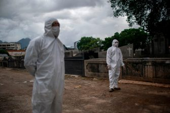 Undertakers wait for the body of a COVID-19 victim at the Caju cemetery in Rio de Janeiro, Brazil, on May 8, 2020, during the Covid-19 coronavirus pandemic. - Brazil has registered more than 135,000 cases of the new coronavirus, with 9,146 deaths so far -- by far the highest figures in Latin America. (Photo by MAURO PIMENTEL / AFP) (Photo by MAURO PIMENTEL/AFP via Getty Images)