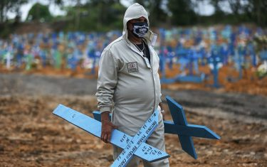Brazilian Ulisses Xavier, 52, who has worked for 16 years at Nossa Senhora cemetery in Manaus, Brazil, prepares to place crosses in graves during his shift on May 8, 2020, amid the new coronavirus pandemic. - Xavier works 12 hours a day and supplements his income by making wooden crosses for graves. The cemetery has seen a surge in the number of new graves after the outbreak of COVID-19. (Photo by MICHAEL DANTAS / AFP) (Photo by MICHAEL DANTAS/AFP via Getty Images)