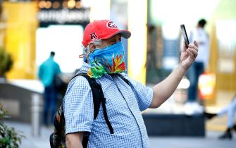 NEW YORK, NEW YORK - MAY 07:  A man wearing a home made mask takes a video in Times Square as daily life continues amid the coronavirus outbreak on May 07, 2020 in New York City. COVID-19 has spread to most countries around the world, claiming over 270,000 lives and infecting over 3.9 million people.  (Photo by John Lamparski/Getty Images)